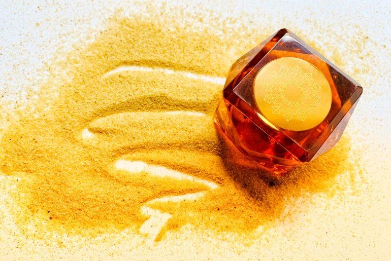 foah perfume bottle in sand